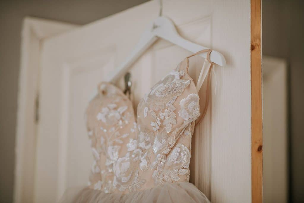 A beautiful lace wedding dress is hanging up ready to go on