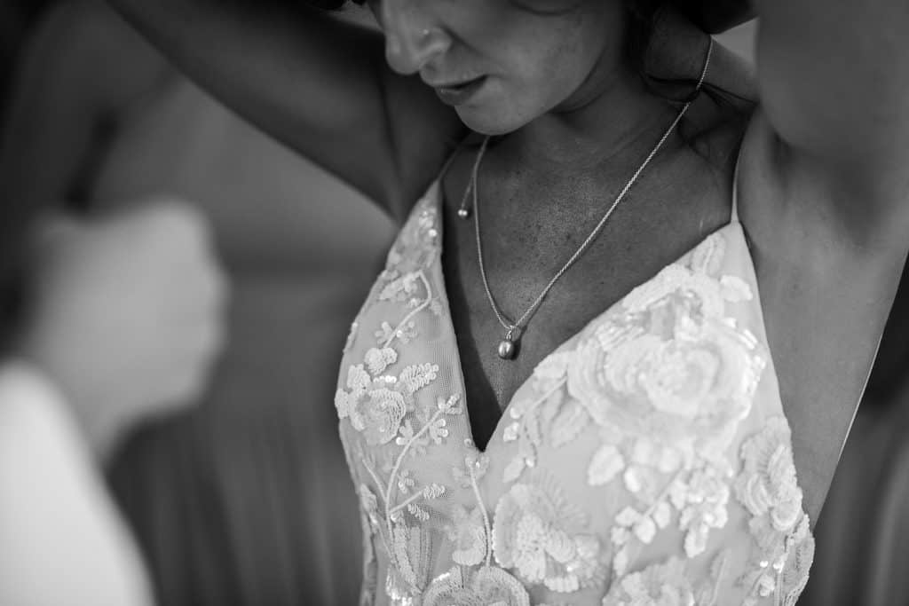 A bride puts on a necklace as she gets ready for her wedding day