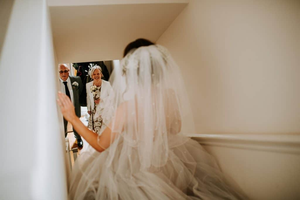 A bride walks down the stairs towards her perants