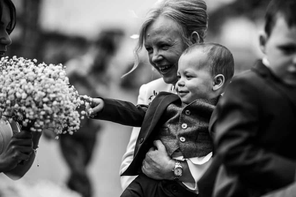 A young boy plays with a bridal bouquet
