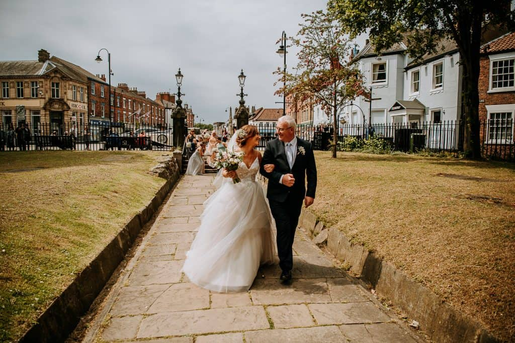 A bride and her dad arrive at the church