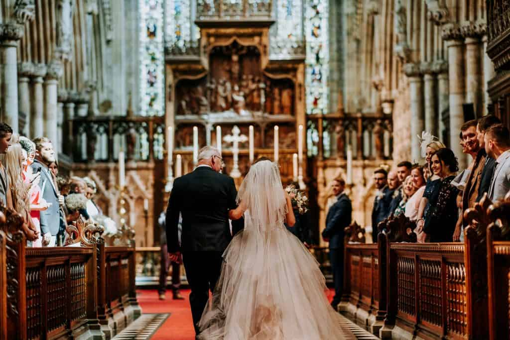 A bride walks into her wedding ceremony within a stunning abbey setting
