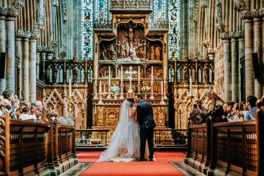 A bride and groom share their first kiss at Selby Abbey