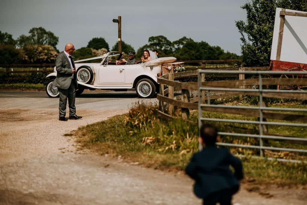 A young boy runs towards a wedding car as it arrives at Berts Barrow wedding venue in Yorkshire