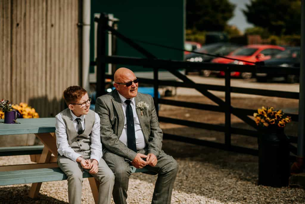 An old man and a young boy enjoy the sun during the wedding reception at Berts Barrow
