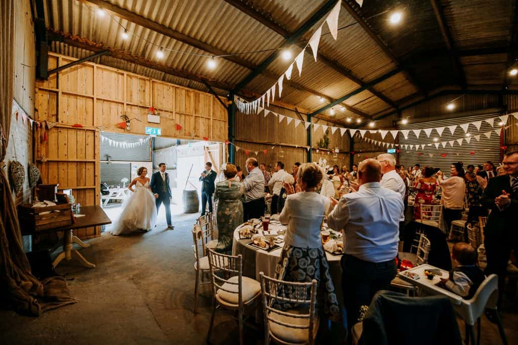 A happy couple enter a beautifully decorated barn on their wedding day
