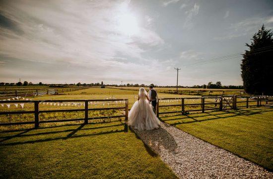 A bride and groom walk together at Berts Barrow wedding venue