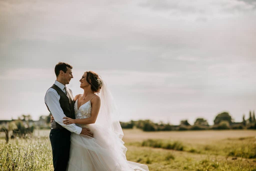 A bride and groom look lovingly at each other as they stand in a green field