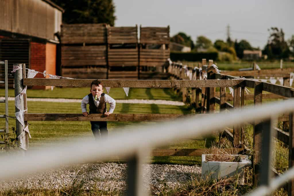 A young boy plays on a fence at Berts Barrow wedding venue