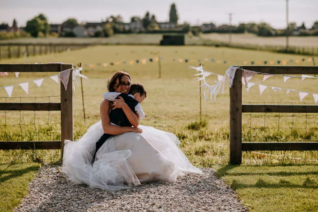 A bride hugs her son close to her on her wedding day