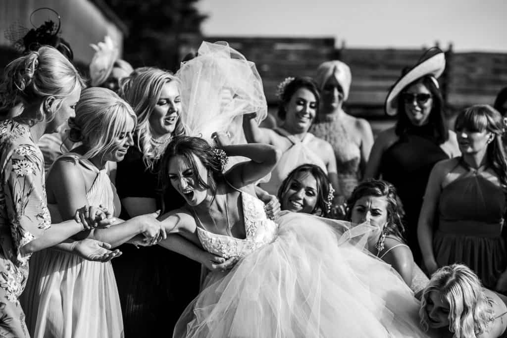 A bride is picked up by her wedding guests