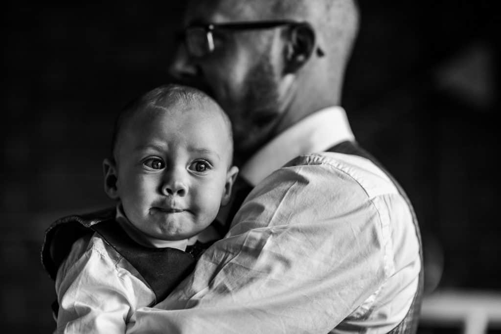 A black and white image of a young wedding guest is held by his dad