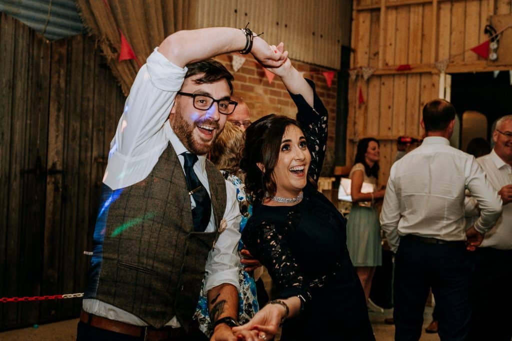Wedding guests laugh and joke together on the dance floor