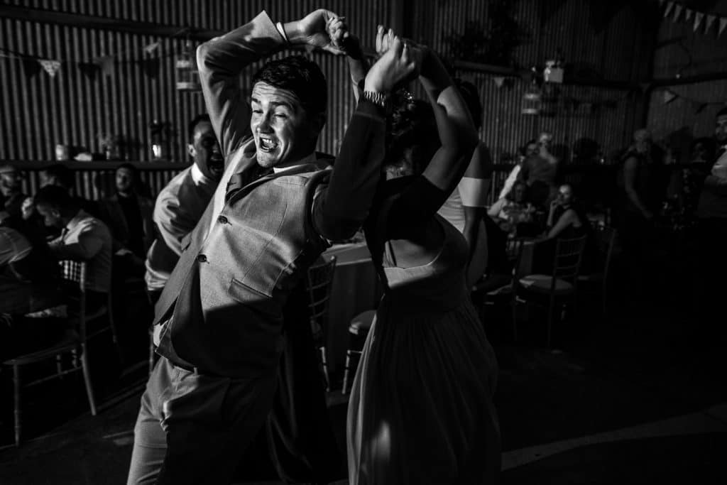 Two wedding guests enjoy dancing together