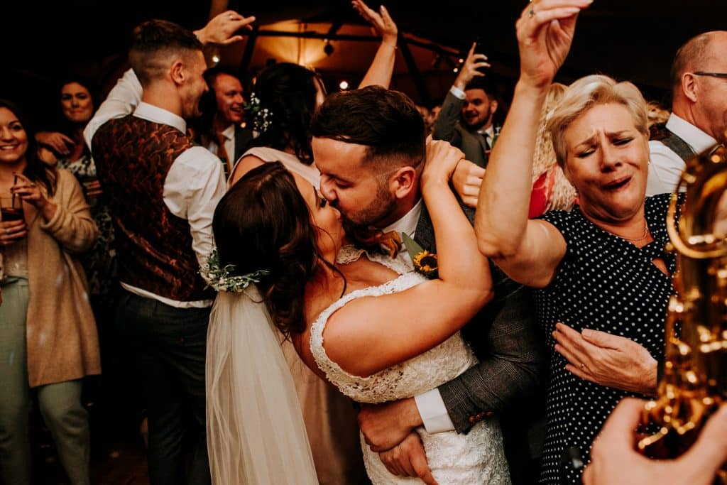 A bride and groom kiss on a busy dance floor captured by Yorkshire Wedding Photographer M and G Wedding Photography
