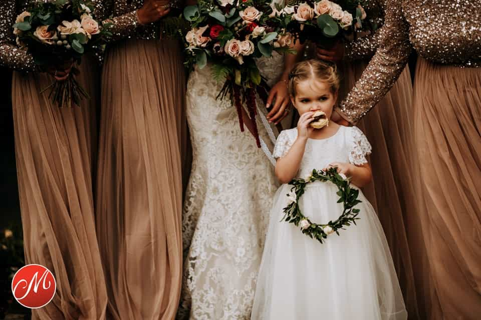 A young girl eats a burger during a wedding day