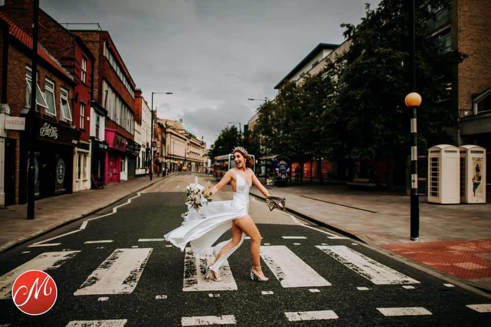 Yorkshire bride strides across a level crossing confidently captured by M and G Wedding Photography