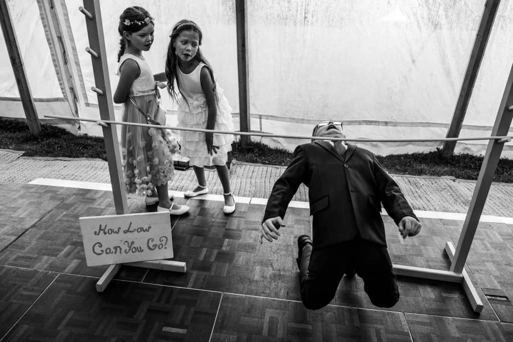 Children playing limbo at a wedding captured by Yorkshire Wedding Photographer M and G Wedding Photography