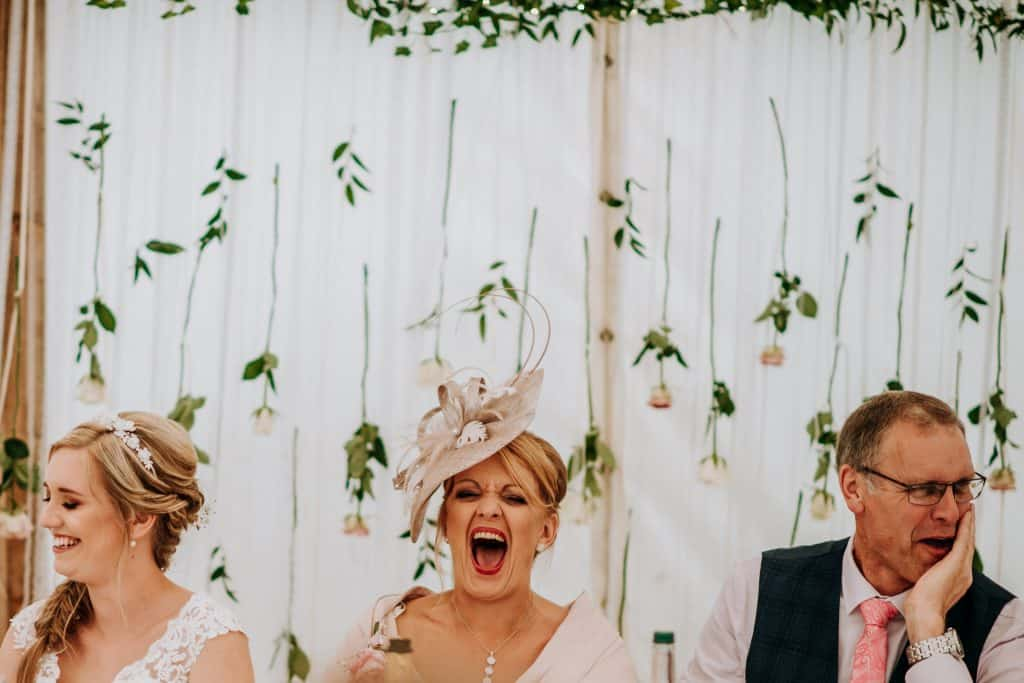 Wedding guests laugh hysterically at wedding speeches