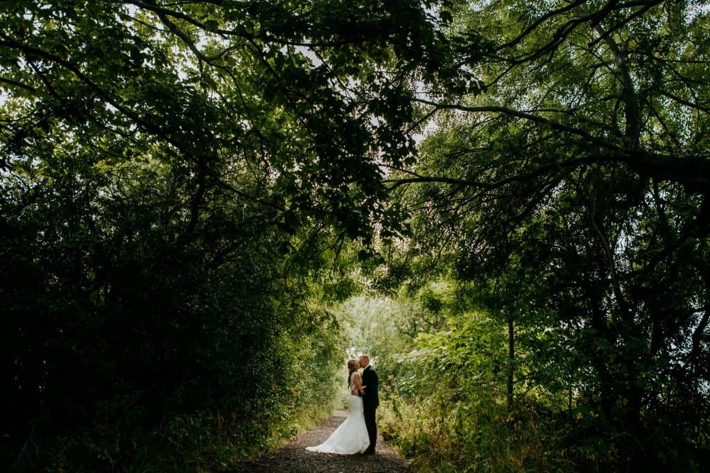 a beautiful couple shot surrounded by greenery at Little Wold Vineyard