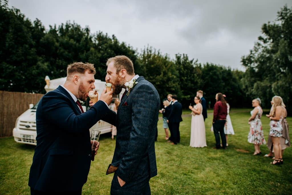 Two men feeding each other ice cream at a wedding