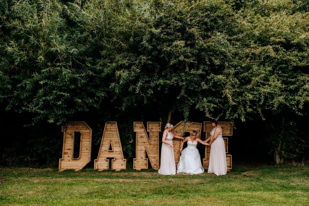 A bride falls over on her wedding day into some large wooden letters spelling Dance