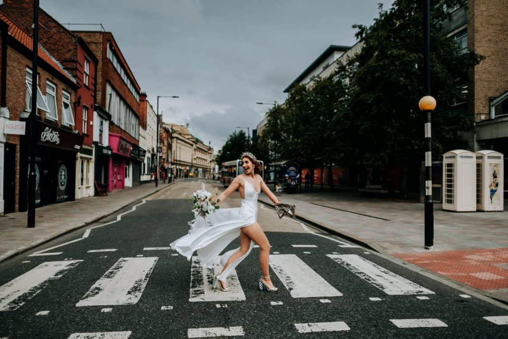 A bride strides across the street by Yorkshire Wedding Photographer M and G Wedding Photography