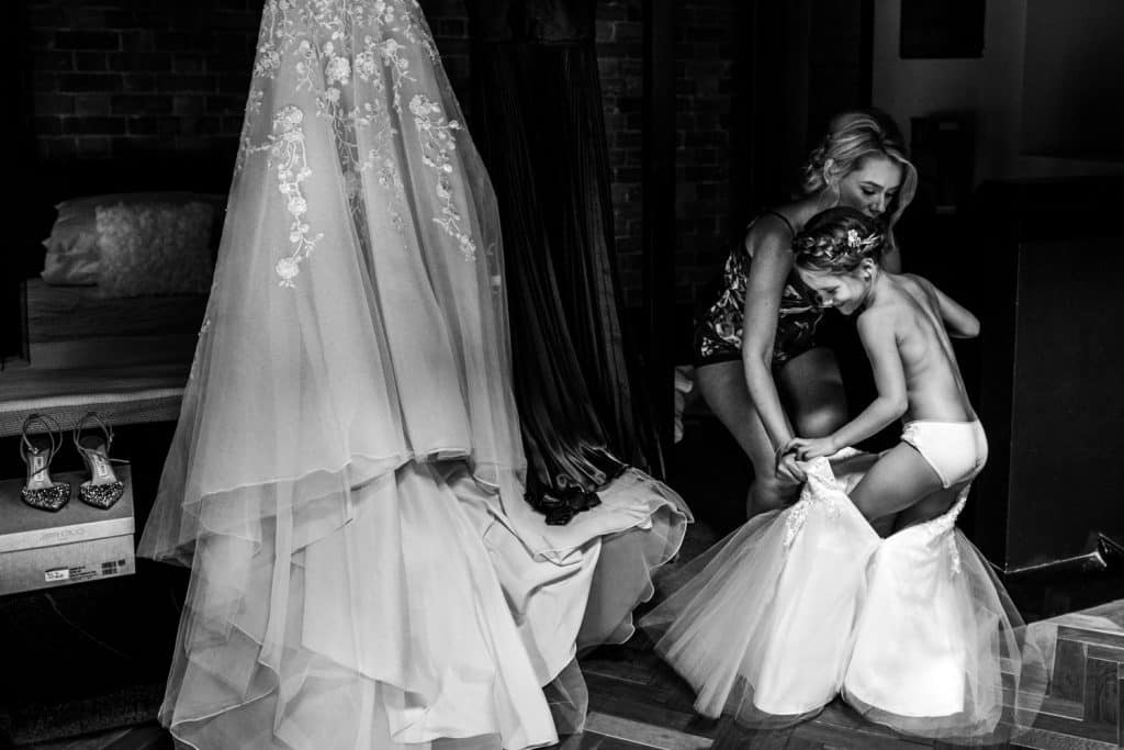 award winning image by Yorkshire Wedding Photographer M and G Wedding Photography of a bride helping her flower girl into her beautiful dress