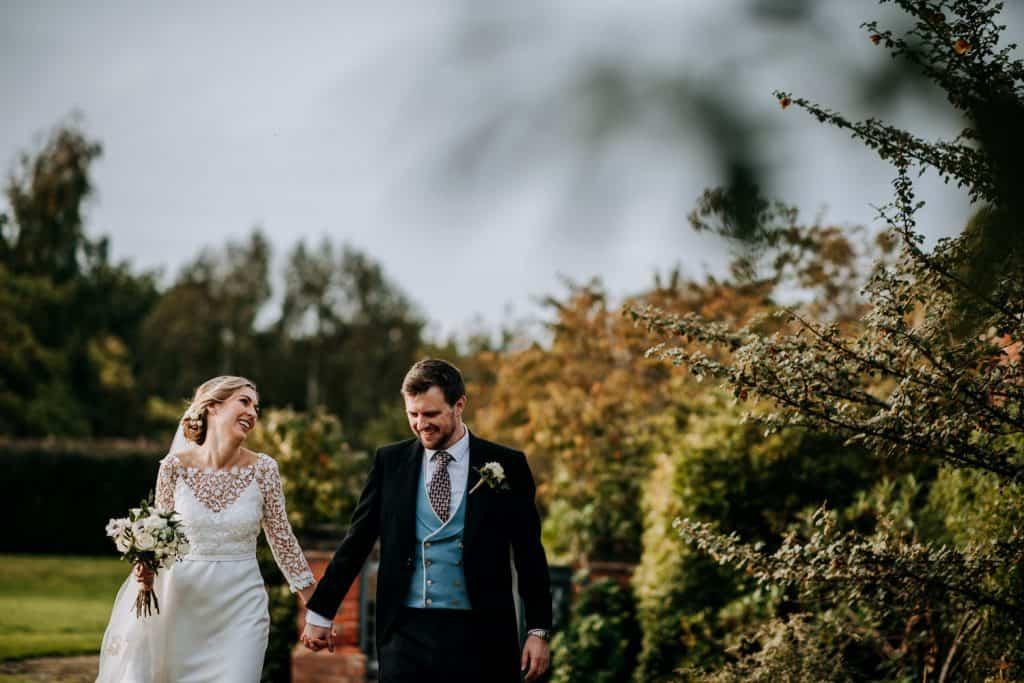 A couple enjoy a romantic walk through some gardens on their wedding day