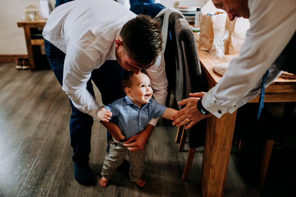 A child smiles as his dad gets him dressed