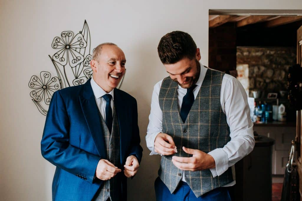 The groom laughs with his dad on his wedding morning