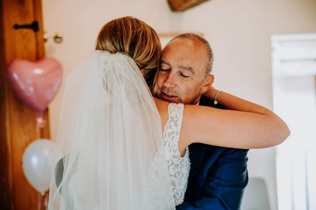 A bride and her dad embrace