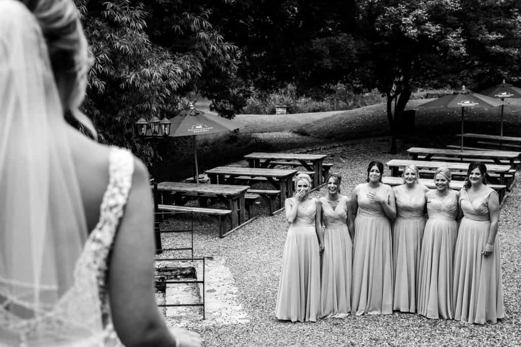 The bride shows her bridesmaids her beautiful bridal gown captured by Stone Barn wedding photographer M and G Wedding Photography