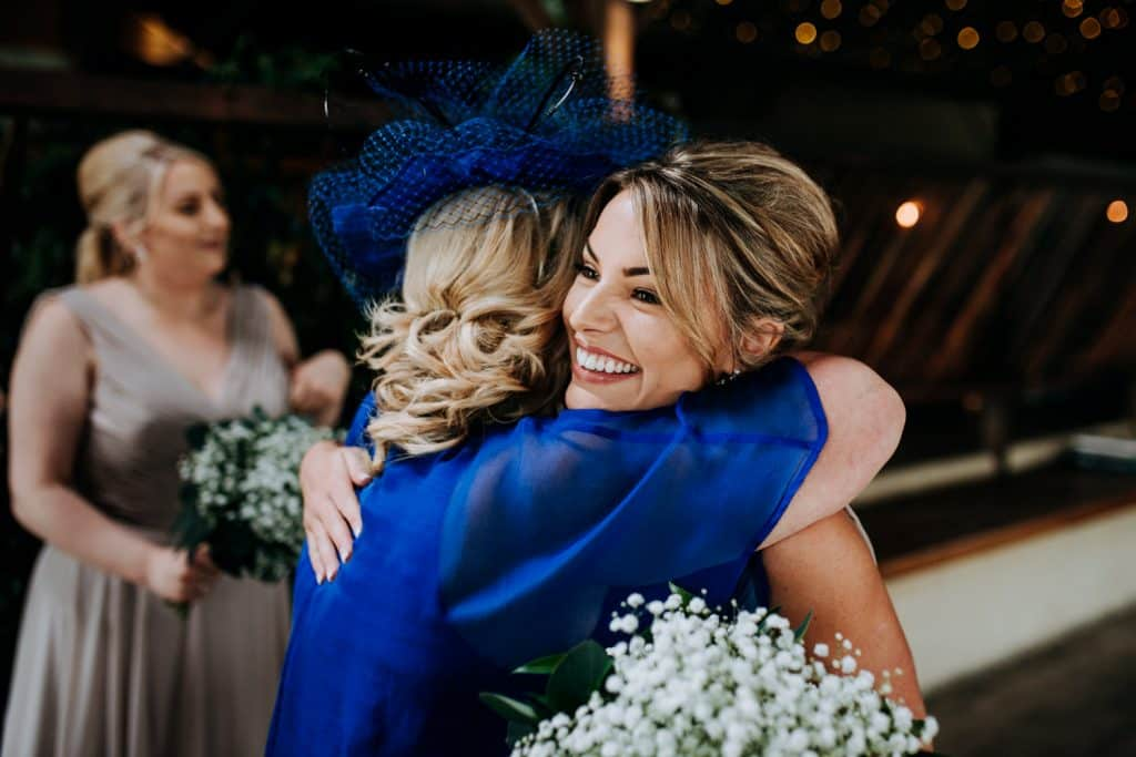 Two wedding guests share a hug at Stone Barn