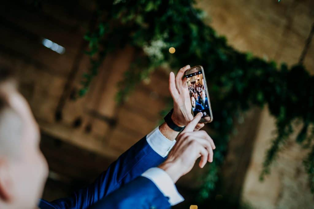 A wedding guest takes a selfie at Stone Barn in the Cotswolds