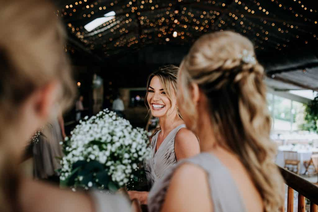 Bridesmaids smile as they await the arrival of the bride photographed by Stone Barn wedding photographer M and G Wedding Photography