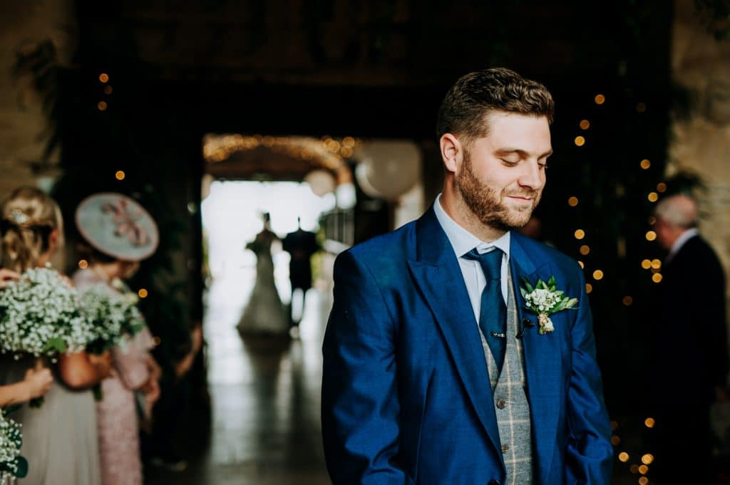 A groom waits as the end of the aisle at Stone Barn as his bride appears in the distance