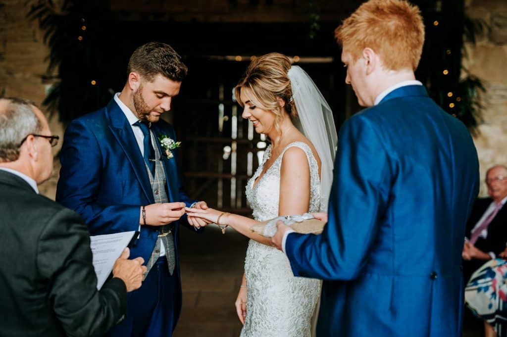 A groom puts on his bride's wedding ring during their barn wedding ceremony