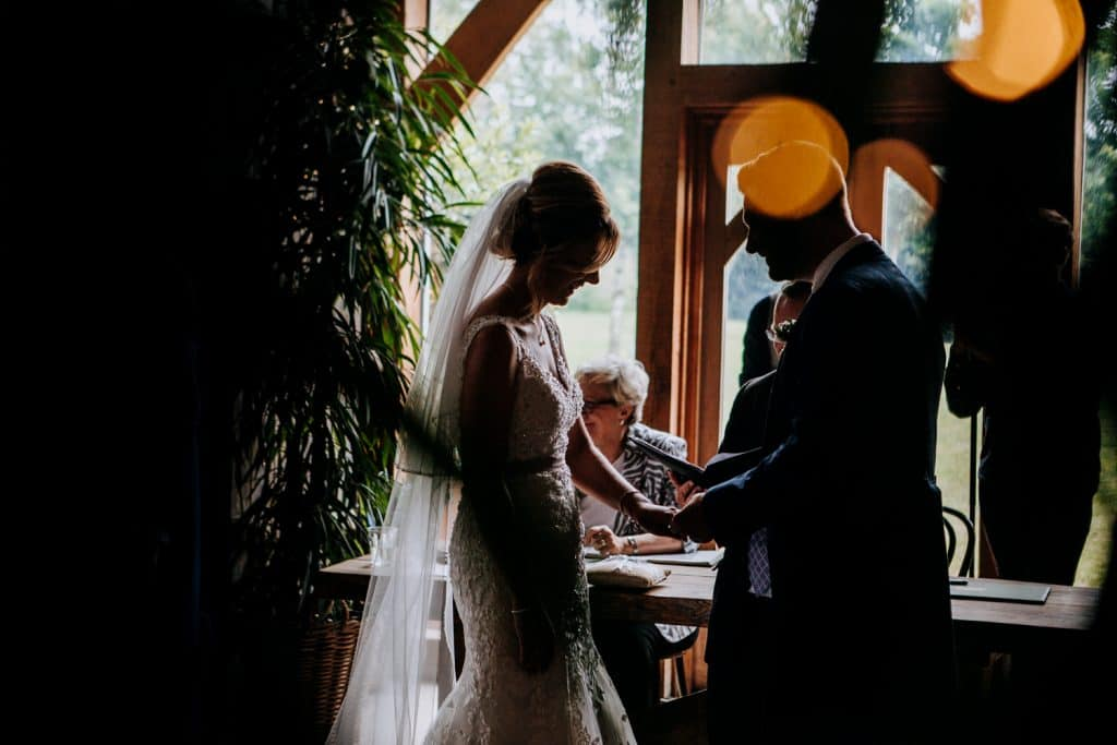 A silhouetted image of a wedding ceremony photographed by Stone Barn wedding photographer M and G Wedding Photography