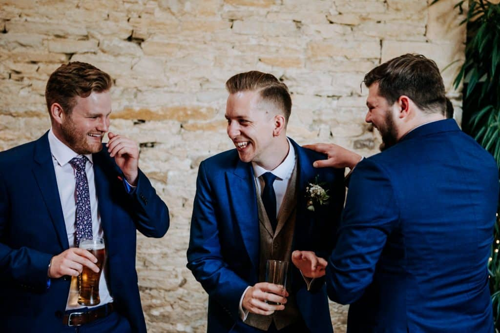 Wedding guests laugh and joke at Stone Barn in the Cotswolds