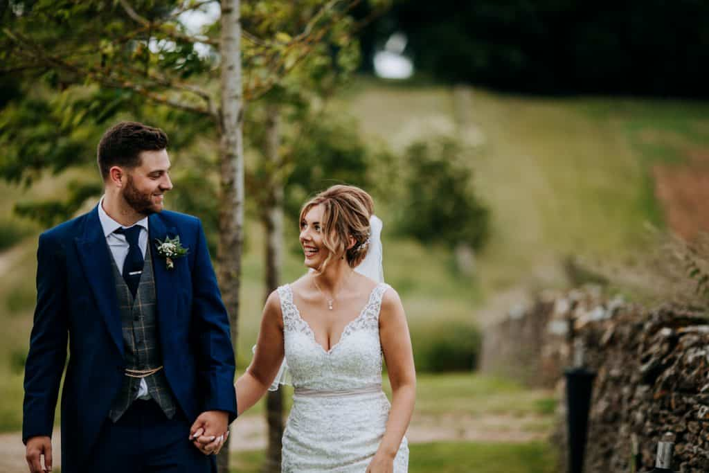 A bride and groom share a romantic walk in the Cotswolds