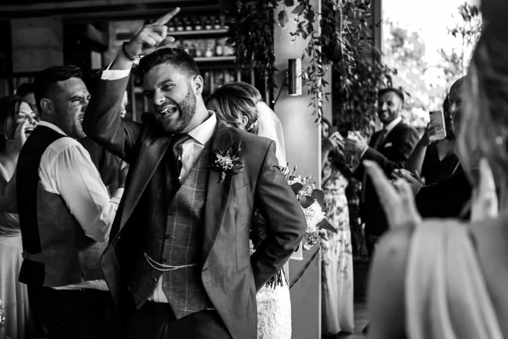 A groom salutes his guests as he enter the room to enjoy the wedding speeches
