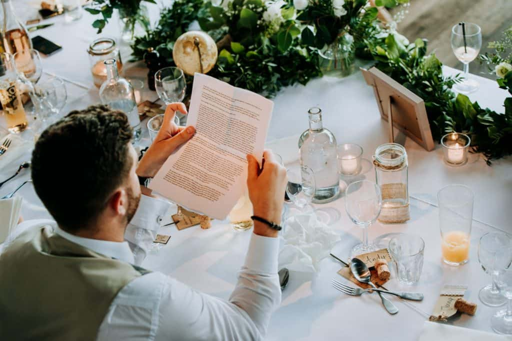 A bride groom carefully reads his wedding speech