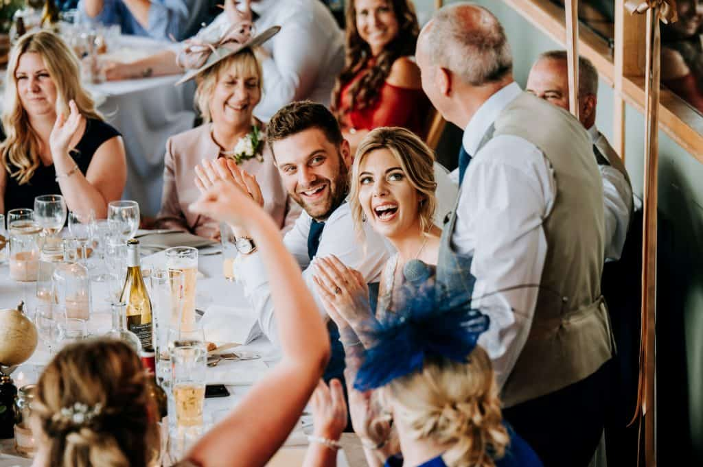 A bride and a groom react with hilarity to the father of the bride's speech