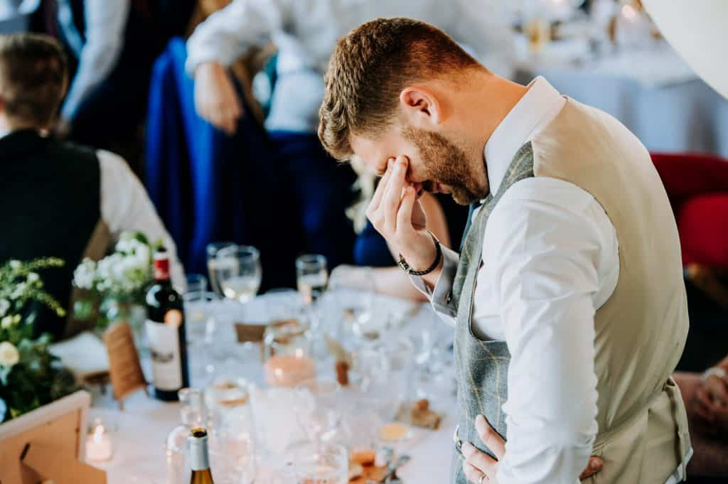A groom wipes away his tears during his speech