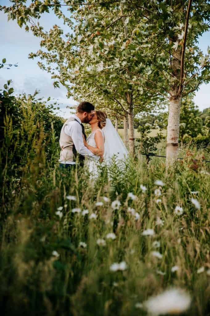 A bride and groom share a kiss in a meadow