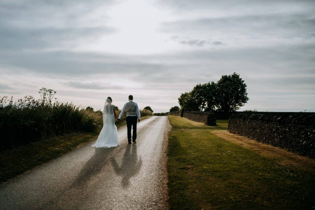 A bride and groom take a romantic walk in the Cotswolds countryside