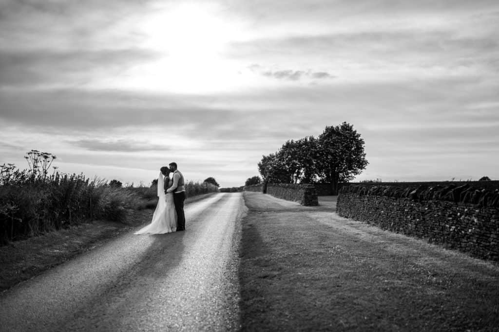 In the middle of an otherwise empty road a bride and groom stop for a romantic and tender kiss