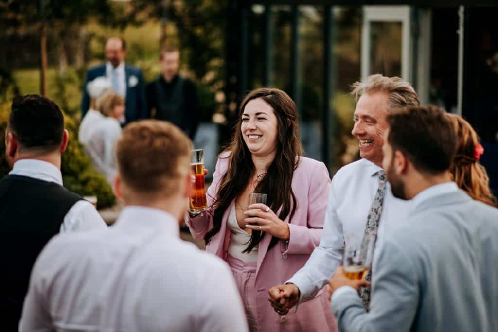 Wedding guests enjoy drinks together at the Cotswolds wedding venue Stone Barn
