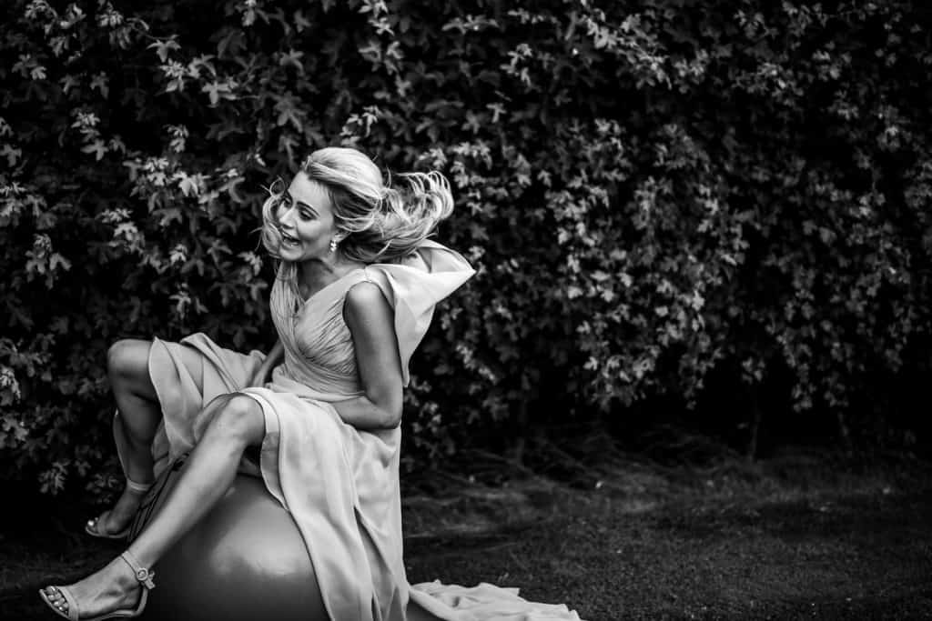 A bridesmaid enjoys using a space hopper - image captured in black and white by Stone Barn wedding photographer M and G Wedding Photography